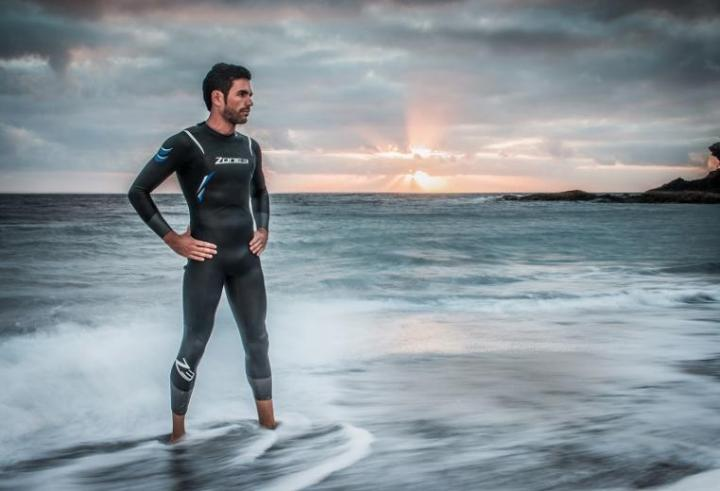 A man posing in a Zone3 wetsuit in the ocean swash