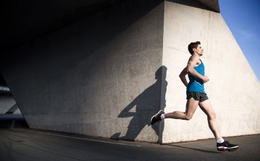 Man running by a wall and his shadow is visible in image