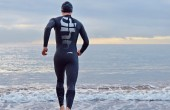 image of swimmer running into water wearing dhb wetsuit