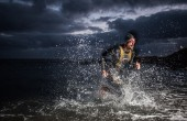 A man sprinting out of the ocean at night wearing a Zone3 wetsuit